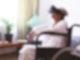 Seniorin sitzt mit VR-Brille im Rollstuhl